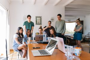 Group of people gathered around a laptop discussing what they see