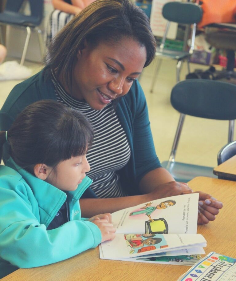 African American woman sitting with a young girl reading a picture book together